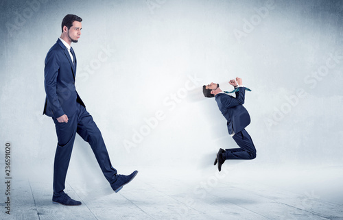 Obraz na plátně Big businessman kicking small businessman who is flying away with his briefcase