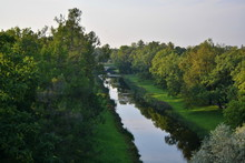 Narrow Long Straight Creek Between Fields With Green Grass And Trees. Top View