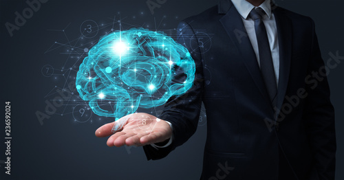 Cuadros en Lienzo  Businessman holding human brain on his hand with logistics symbols around