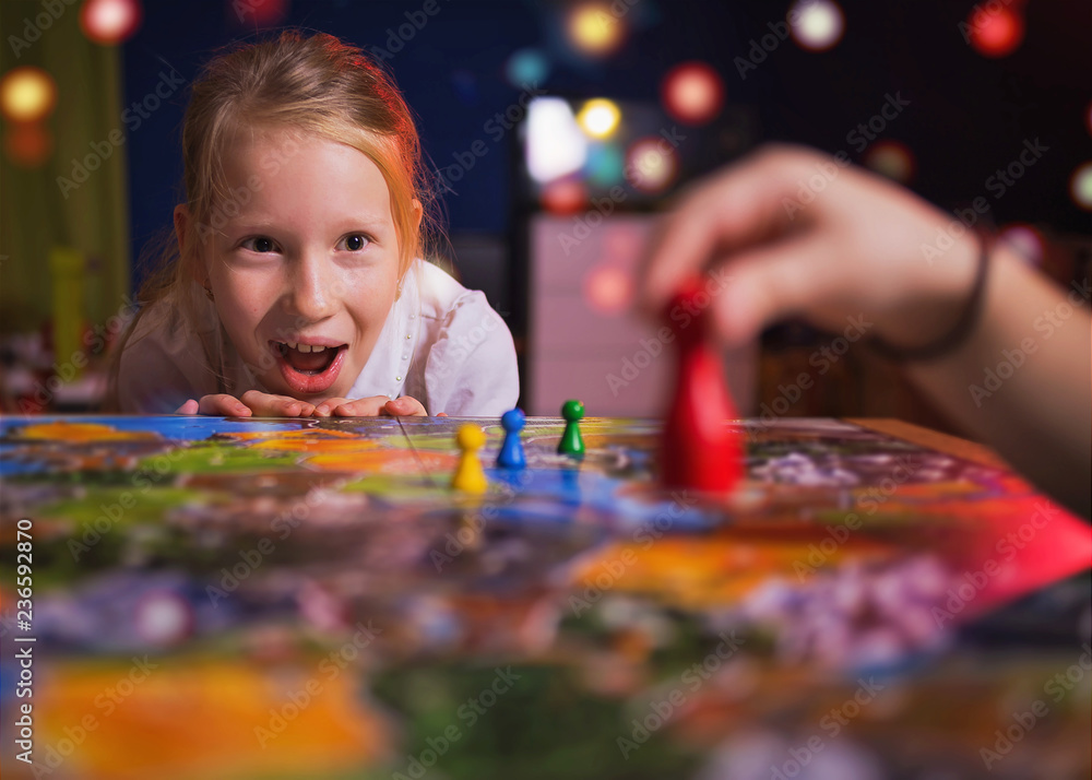 Fototapeta Board game concept - your move. Little girl watched the game and shock from the action move. Board game field, many figures. Kid girl play in board game at home on dark blurred background