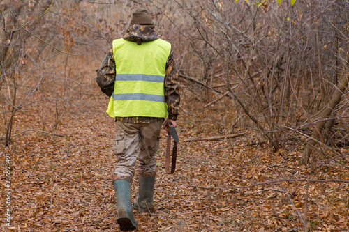 Foto op Canvas Jacht Hunter with a gun and a dog go on the first snow in the steppe, Hunting pheasant in a reflective vest
