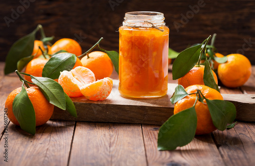 glass jar of tangerine jam with fresh fruits