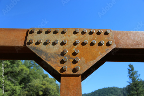 Fotografie, Obraz  rusted steel connection with bolts with blue sky background