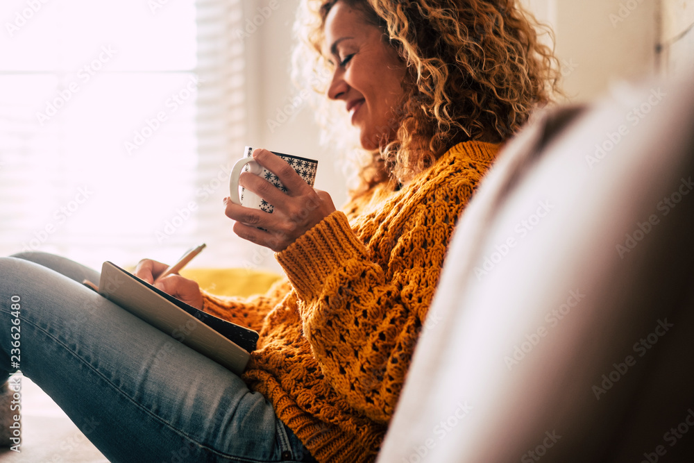 Fototapeta Happy cute lady at home write notes on a diary while drink a cup of tea and rest and relax taking a break. autumn colors and people enjoying home lifestyle writing messages or lists. Blonde curly