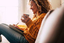 Happy Cute Lady At Home Write Notes On A Diary While Drink A Cup Of Tea And Rest And Relax Taking A Break. Autumn Colors And People Enjoying Home Lifestyle Writing Messages Or Lists. Blonde Curly
