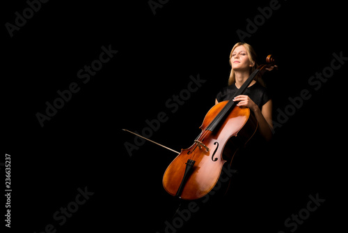 Fotomural Young girl playing the cello on isolated black background