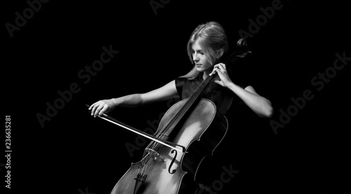 Young girl playing the cello on isolated black background - 236635281