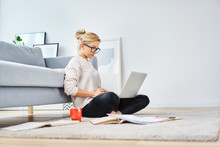 Young Woman Sitting On Floor At Home Working With Laptop And Documents