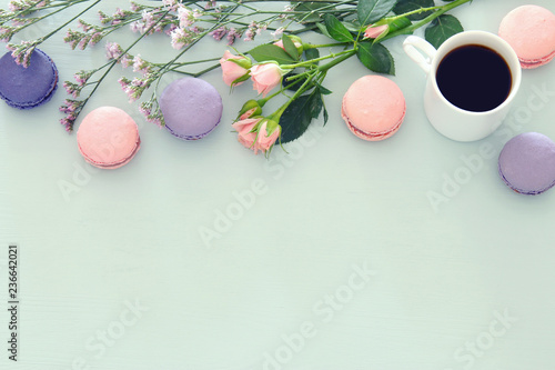 Foto auf AluDibond Macarons Top view image of white cup of coffee and colorful macaron or macaroon over pastel wooden background.