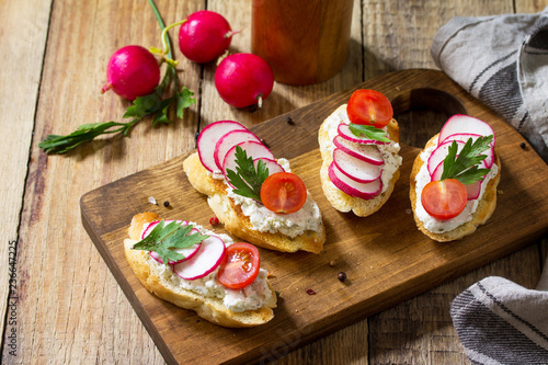 Antipasti snacks for Wine. Brushetta or Crostini with Toasted Baguette, Cheese, Radish and Tomatoes on a wooden table.