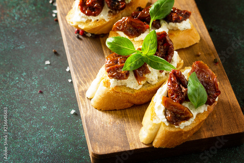 Foto op Plexiglas Voorgerecht Italian Antipasti snacks for Wine. Brushetta with Soft Cheese and Dried Tomatoes served on a rustic wooden board on a stone table. Copy space.