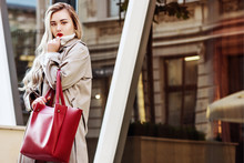 Outdoor Fashion Portrait Of Young Beautiful Fashionable Girl Wearing Trendy Beige Long Trench Coat,  Holding Big Red Handbag, Model Posing In Street Of European City. Copy, Empty Space For Text