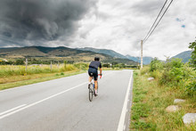 A Cyclist Riding Towards Storm Clouds Above Mountains