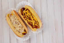 Two Hot Dogs One With Sauerkraut And Another With Chili Cheese Toppings On A White Ewood Table With Copy Space.