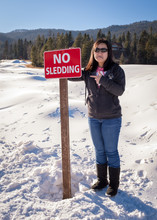 Small Asian Girls Shows Sad Face With No Sledding Sign
