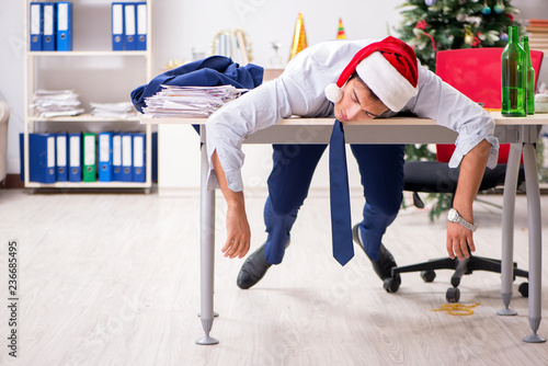 Fotografering  Young handsome employee celebrating Christmas at workplace