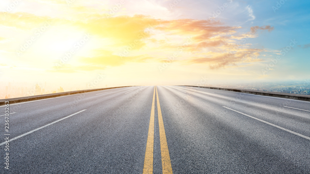 Fototapeta Panoramic city skyline and buildings with empty asphalt road at sunset