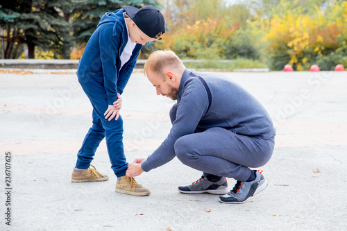 Fotografía  Father tying shoelace of son while playing in a park