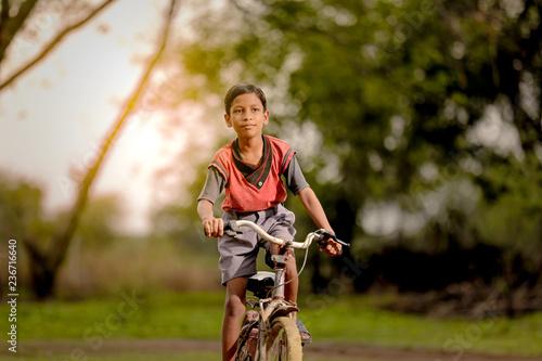 Fotografia indian child on bicycle