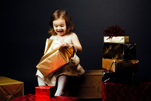 Excited Toddler Girl Opening A Golden Gift With Joy, Against A Black Studio Background