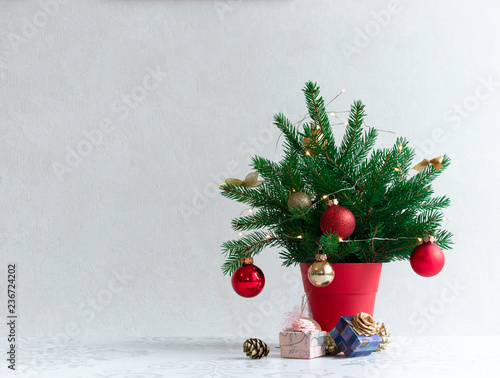 Photo Stands Roe on a light background there is a Christmas decorated tree in a red pot under it