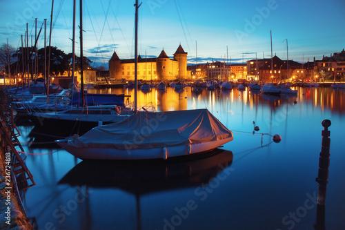 Plakat MORGES, SZWAJCARIA - 5 marca 2018: Piękna nocna panorama z zamkiem Morges i łodziami w porcie