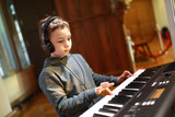 Boy playing on synthesizer