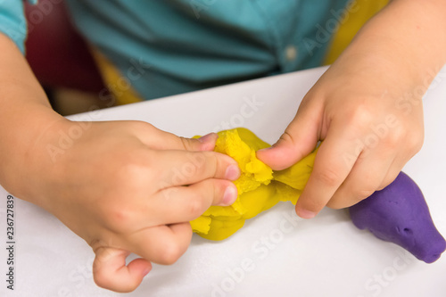 Four year old caucasian boy makes with hands animal figures from modeling yellow clay on white tabletop. Kids creativity preschool education hobby concept