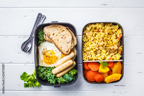 Fototapeta Meal prep containers with rice with chicken, baked vegetables, eggs, sausages and salad overhead shot. obraz