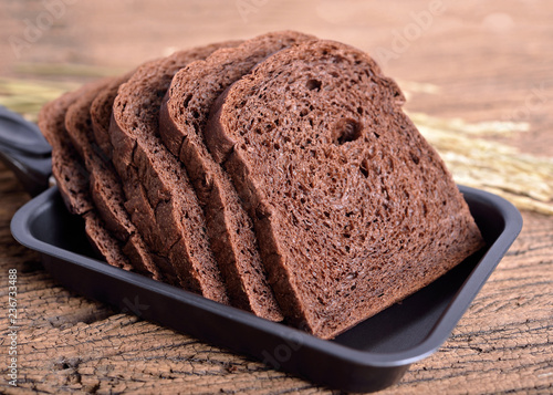 fresh sliced dark cocoa bread in pan on wooden background