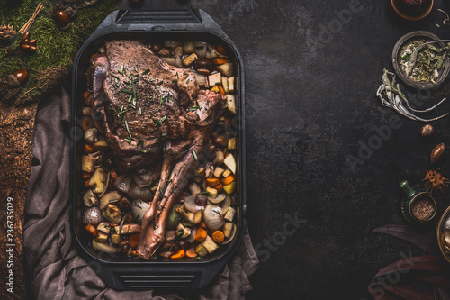 Fototapeta Cooking preparation of venison roast. Leg of deer with bone in cast iron pan with gut vegetables on dark kitchen table background with herbs and spices. Copy space for your recipe or design obraz