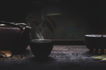 Dark tea background with black iron asian teapot and mug of hot tea with steam on table. Copy space for your design. Authentic vintage style. Traditional tea ceremony arrangement
