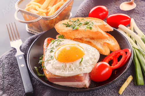 Fried egg with bacon in a black plate with fried pieces of bread, greens tomatoes and French fries on a gray wooden table. Close-up