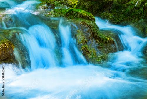 Fotografia  closeup creek rushing among a stones