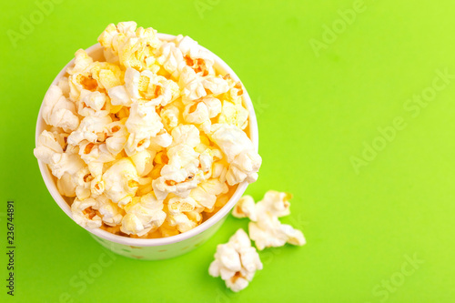 Fotografie, Tablou  Tasty salty popcorn in paper cup on bright green backgraund