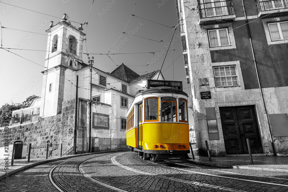 Fototapeta Black and white picture of a yellow tram on the streets of Lisbon, Alfama, Portugal near Santa Luzia church
