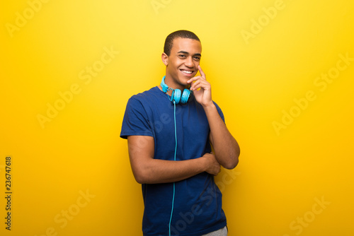 African american man with blue t-shirt on yellow background smiling with a sweet expression - 236747618