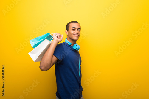 Fototapeta African american man with blue t-shirt on yellow background holding a lot of shopping bags obraz
