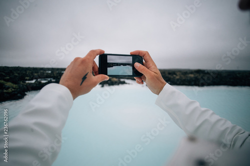 Valokuva Adventurer tourist or travel blogger makes photos of blue lagoon sulfur geotherm
