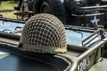 Green Military Helmet With Net On A Vehicle