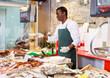 Salesman preparing fish for sale