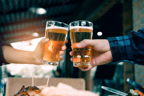 Tuinposter Bier / Cider Close up of hand people friends toasting and clinking with glass of beer in restaurant.