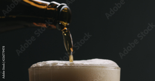 Photo Closeup pour dark beer from brown bottle into glass on black background