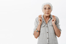 Waist-up Shot Of Energzied Worried Hopeful Granny With White Hair In Casual Shirt Clenching Teeth Crossing Fingers For Good Luck Watching Lottery On Tv And Hoping Win Money Posing Over Grey Background