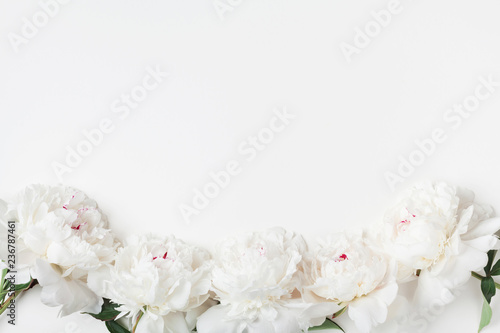 Empty notebook and gift or present box decorated white peony flowers on pastel table top view. Flat lay composition for birthday or wedding.
