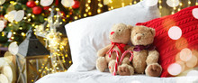 Two Teddy Bears Siting On The Bed With Red Candys Near Christmas Tree. Long Banner