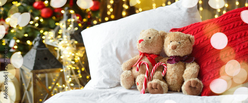 Cuadros en Lienzo Two teddy bears siting on the bed with red candys near christmas tree
