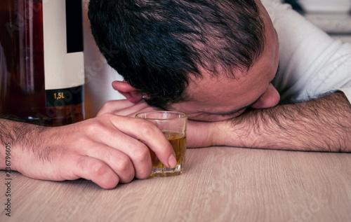 Fotografija  Alcoholic drink and drunken man in kitchen