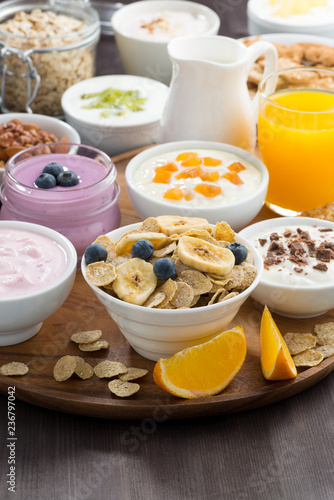rich breakfast buffet with cereals, yoghurt and fruit on wooden tray, vertical