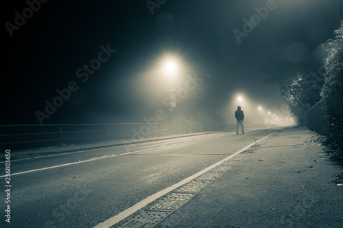 Fotografía  A lone hooded figure standing in the middle of the road on a spooky, foggy night